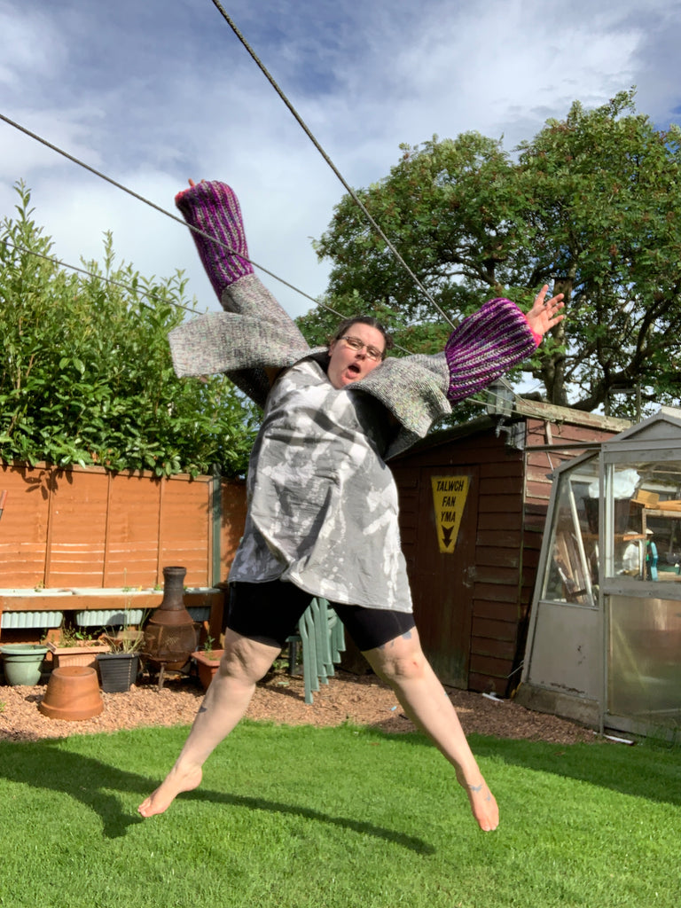 women standing in the middle of a patch of garden jumping in the air wearing a bleach stained denim dress, black chub rub shorts and a giant grey bodied cardigan with purple and grey brioche sleeves