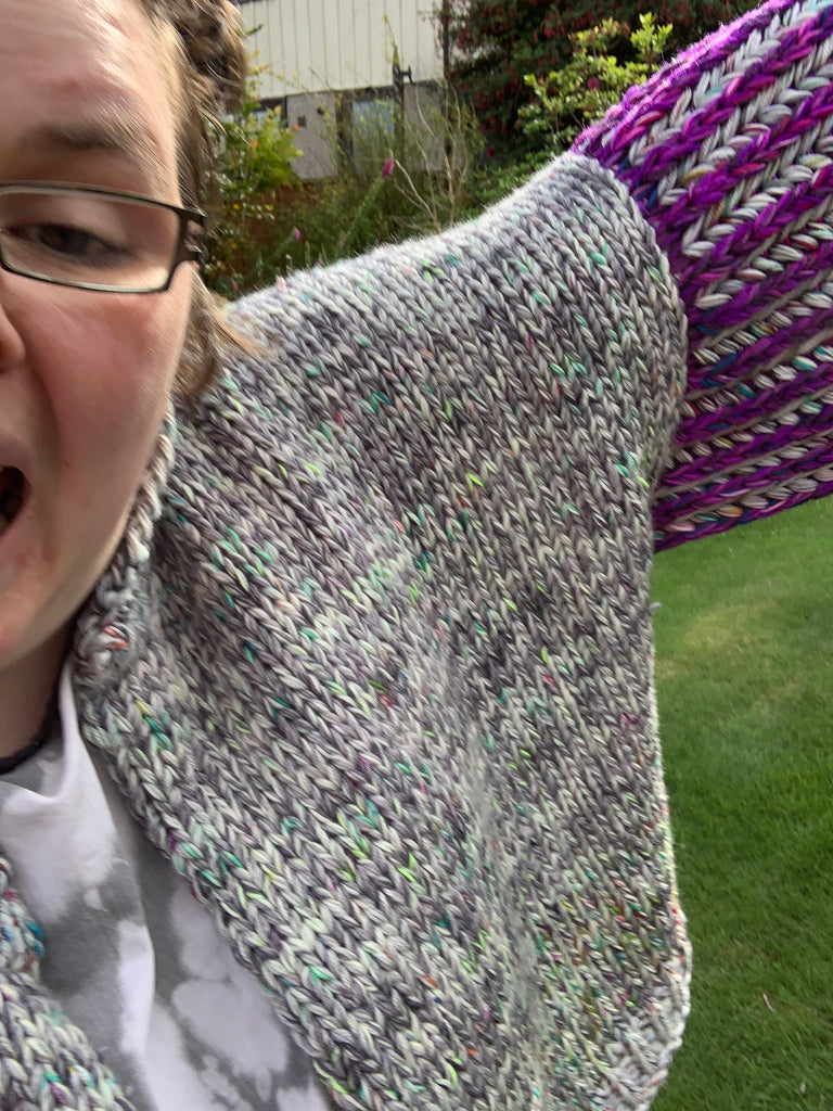 very close up of grey knitted cardigan body with the side of a womans face and her glasses and a tiny bit of purple and grey brioche sleeves