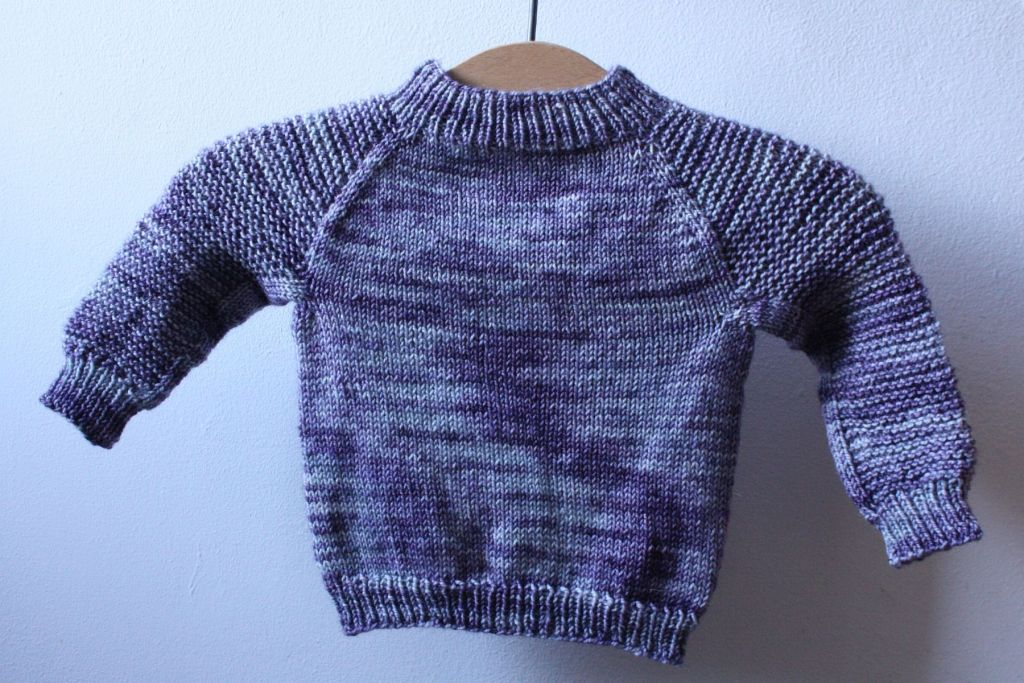 a teeny baby jumper hung on a vintage wooden hanger. its a light purple/lilac verigated jumper on a white wall