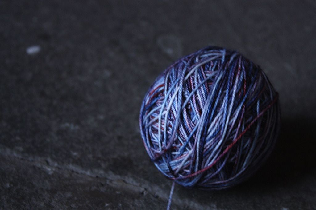 ball of blue and orange speckled yarn hand wound ball on a concrete floor.