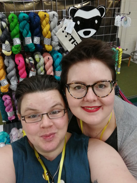 a picture of me on the left and hannah on the right smiling for the camer with yarn in the background and hanging up at perth festival of yarn 2020