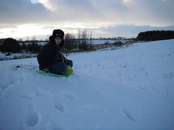 lj on a disk sled all wrapped up going down a hill of snow with a beautiful wintery sky in the backgroud