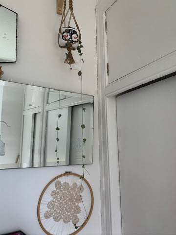 picture is of a wall that has a large vintage mirror in the centre, a slither of another vintage mirror above it to the left. a trailing string of hearts with only two strings hanging from a macramae plant holder in a day of the dead plant pot. under the middle mirror is a cream piece of needle tatting in a large embroidery hoop