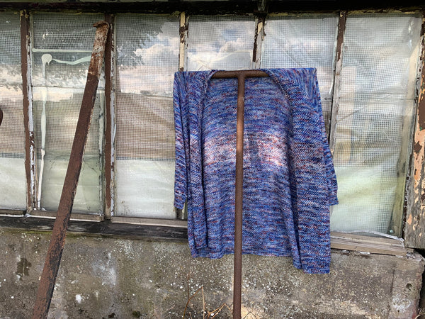 the cardigan is now hanging with its back to us on a big rusty T pole. leaning against a really broken glass out house.
