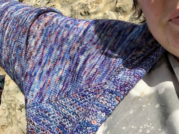 really upclose picture of Ljs shoulder and arm outstreched showing off the knitted cardigan in all its blue, orange and teeny bits of white glory.