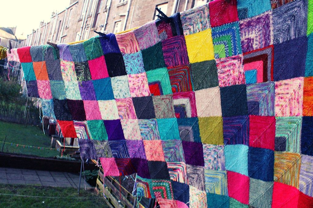 a half made blanket is hanging on a high up washing line. only a diagonal half is made and each square is a different colour. underneeth you can see the garden its hanging about.