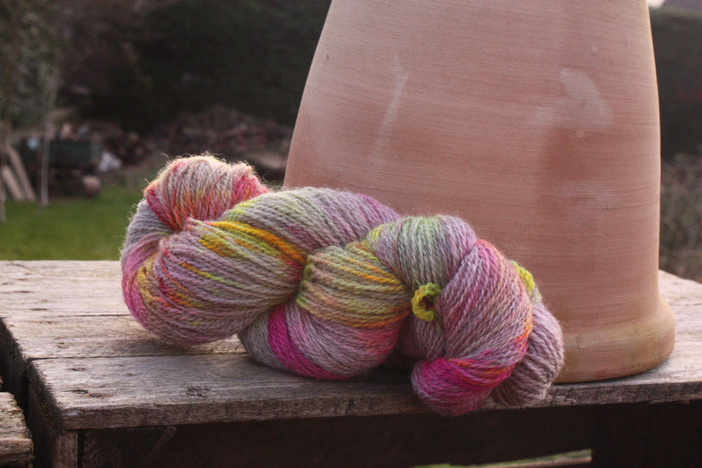 skein of neon pink and yellow yarn sat on a wooden crate next to an upside down terracotta plant pot