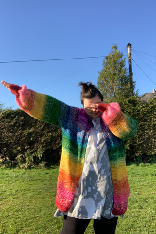 I am stood in the middle of a park. there is a high hedge in the distance, the grass is green and the sky is very blue. I am wearing a bleach stained dress (on purpose) and a rainbow oversized cardigan. it starts at red on the bottom, works its way up the body through orange yellow and green. it gets to blue where the sleeeves join and then fnished in purple. the sleeves do the same kind of pattern. starting at red on the cuff and landing at blue where they join the body. I am dabbing because i am very cool. my hair is up in a little top knot cause covid hair.