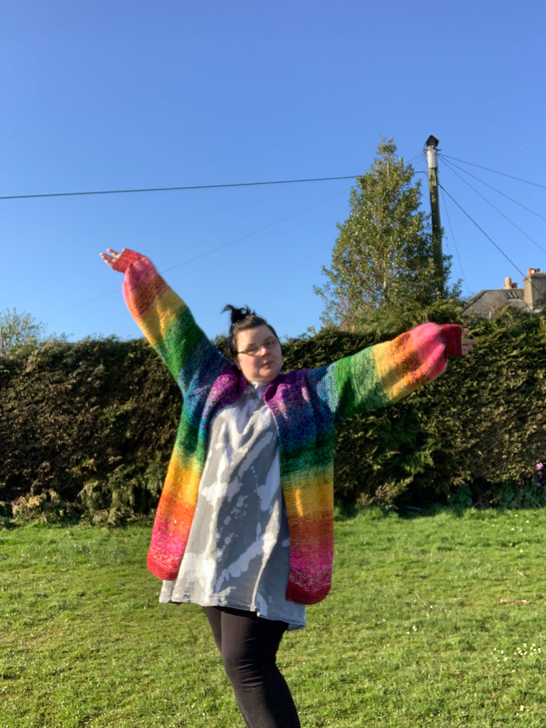 "a women (me) with dark hair scraped into a bun glasses wearing a denim dress thats covered in ""designer"" bleach stains and black leggins, i have my arms in the air and im wearing the roy g biv cardigan. its a long cardigan down past my bum and the colours start at red and go through the rainbow up to the collar. the sleeves do the same"