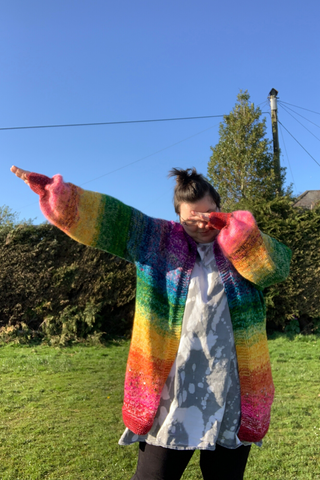 a picture of me (lj) standing in a green grassy park with a big hedge in the background and blue skies. i am dabbing to the left and i am wearing an intentionally bleached stained dress and a huge rainbow cardigan. it is a roughly just bleow the bum cardi and starts at red and goes through the rainbow ending a violet at my neck. the sleeves do the same and they join at the blue portion.