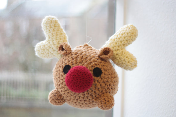 giant crochet raindeer handing with invisible thread in a window. he is very round. body is tan. big red nose. cute black eyes. white antlers