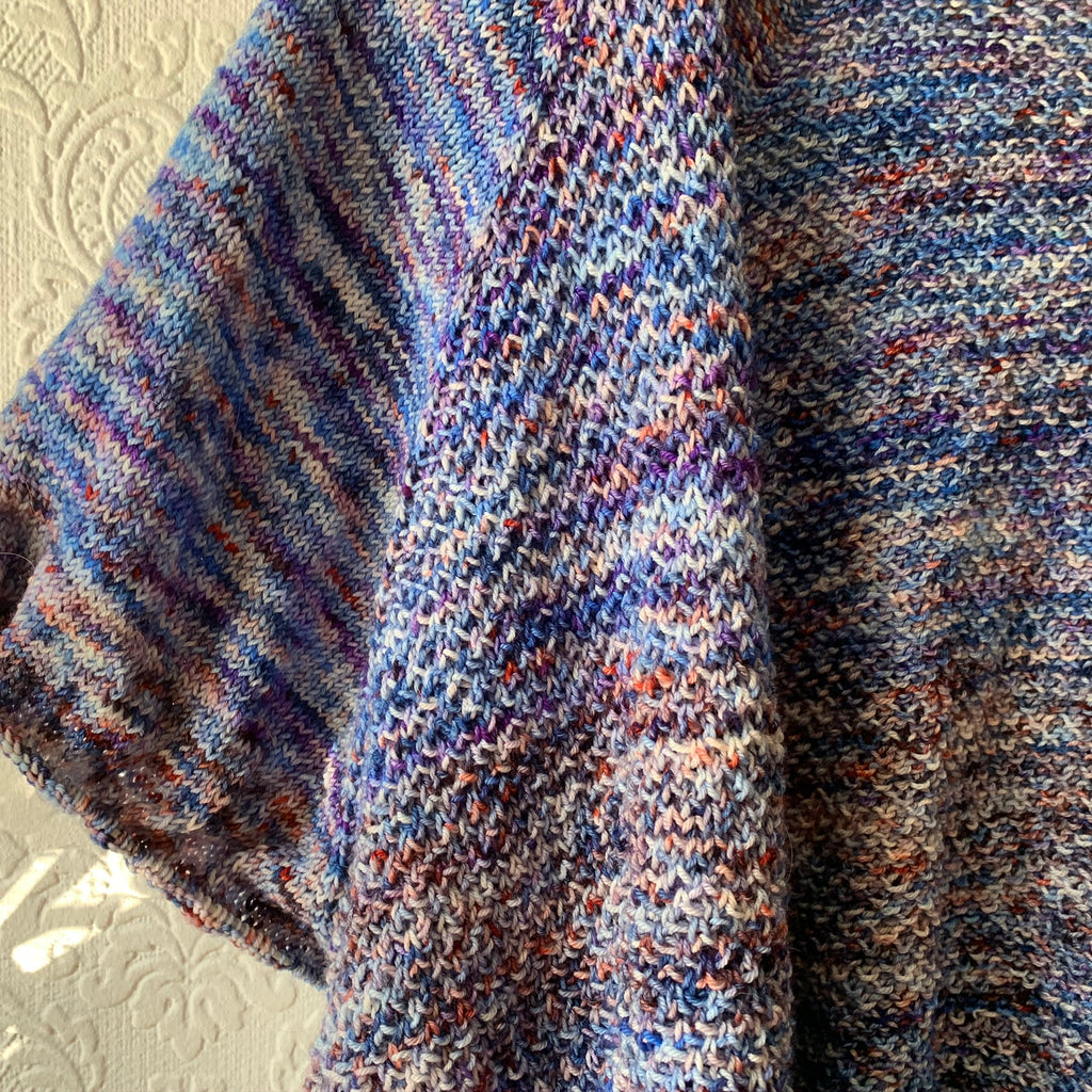 close up of the maema cardigan. its against a white paded wallpaper and sleeveless. you can see the stitch defintion form the broken brioche. the cardigan is dark blue, purply blue and flecks of orange. really heavily verigated