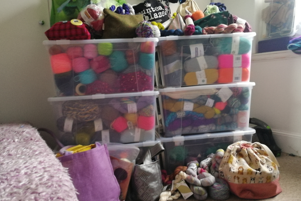 6 large boxes stacked in two rows of three, filled to the brim with yarn. piles of project bags and loose skeins are on the floor and ontop of the boxes