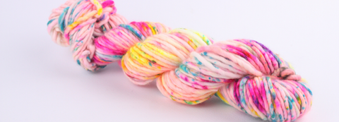 a skein of neon speckled superchunky yarn on a white background. its a natural coloured yarn with pink, yellow and blue speckles