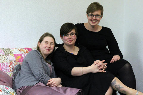 three women sitting on a sofa that is covered in a handmade pink and white quilt. the two on the right are wearing black dresses and the one on the left has a grey cardigan covering a light pink dress