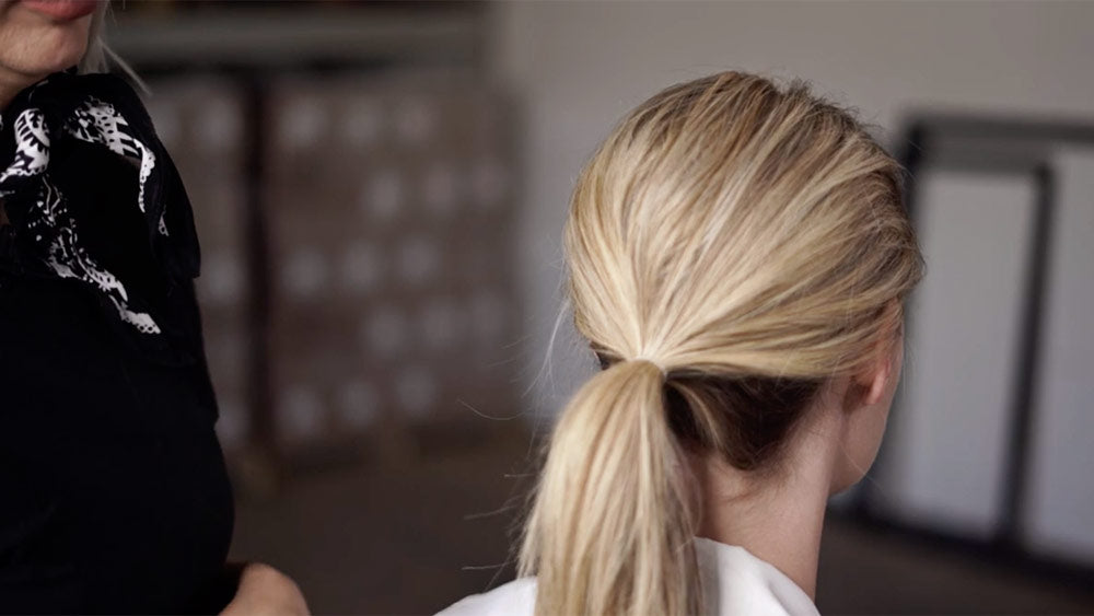 low chignon tutorial pull hair back into low ponytail