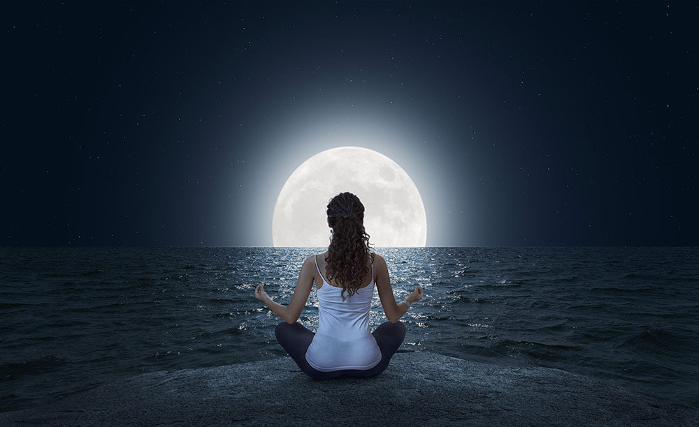 woman sitting on the beach meditating in from of full moon