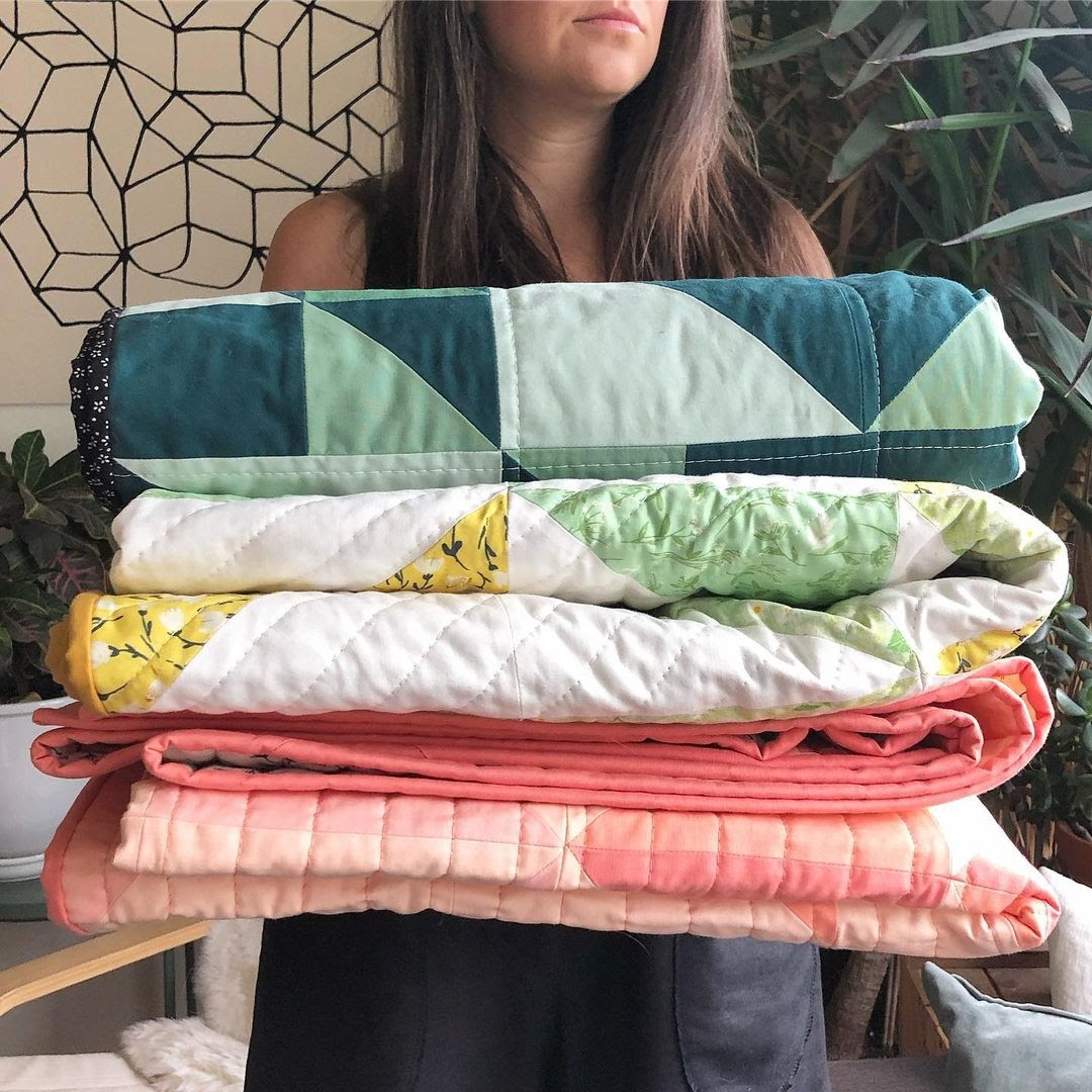 Erin Holding Stack of Birds Hill Quilts