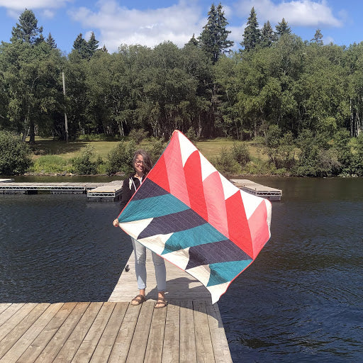 Erin On Dock Holding Stitch and Repeat Pine Falls Quilt