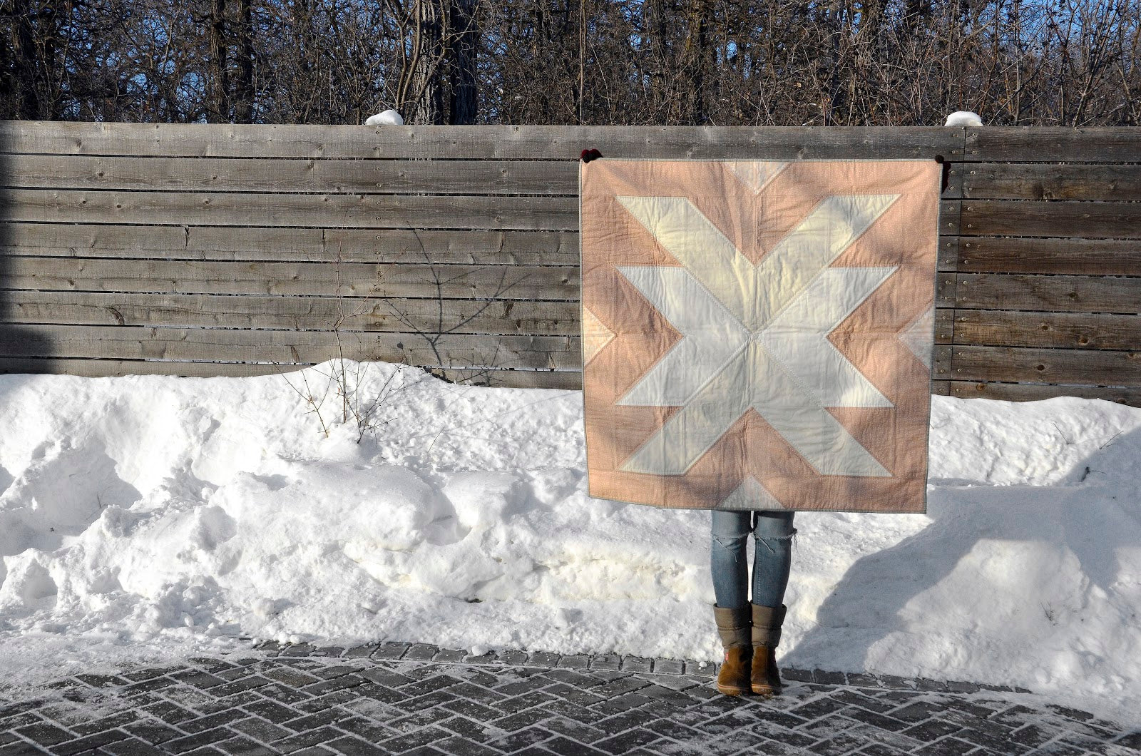 Holding Up Pink Cross Lake Quilt In Snow 2