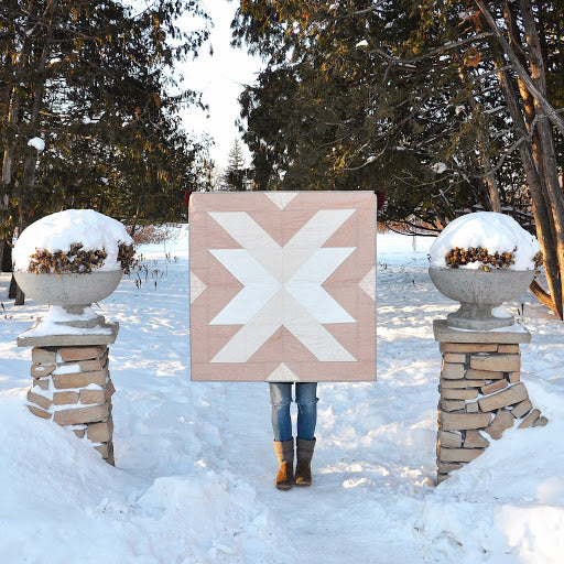 Holding Up Pink Cross Lake Quilt In Snow