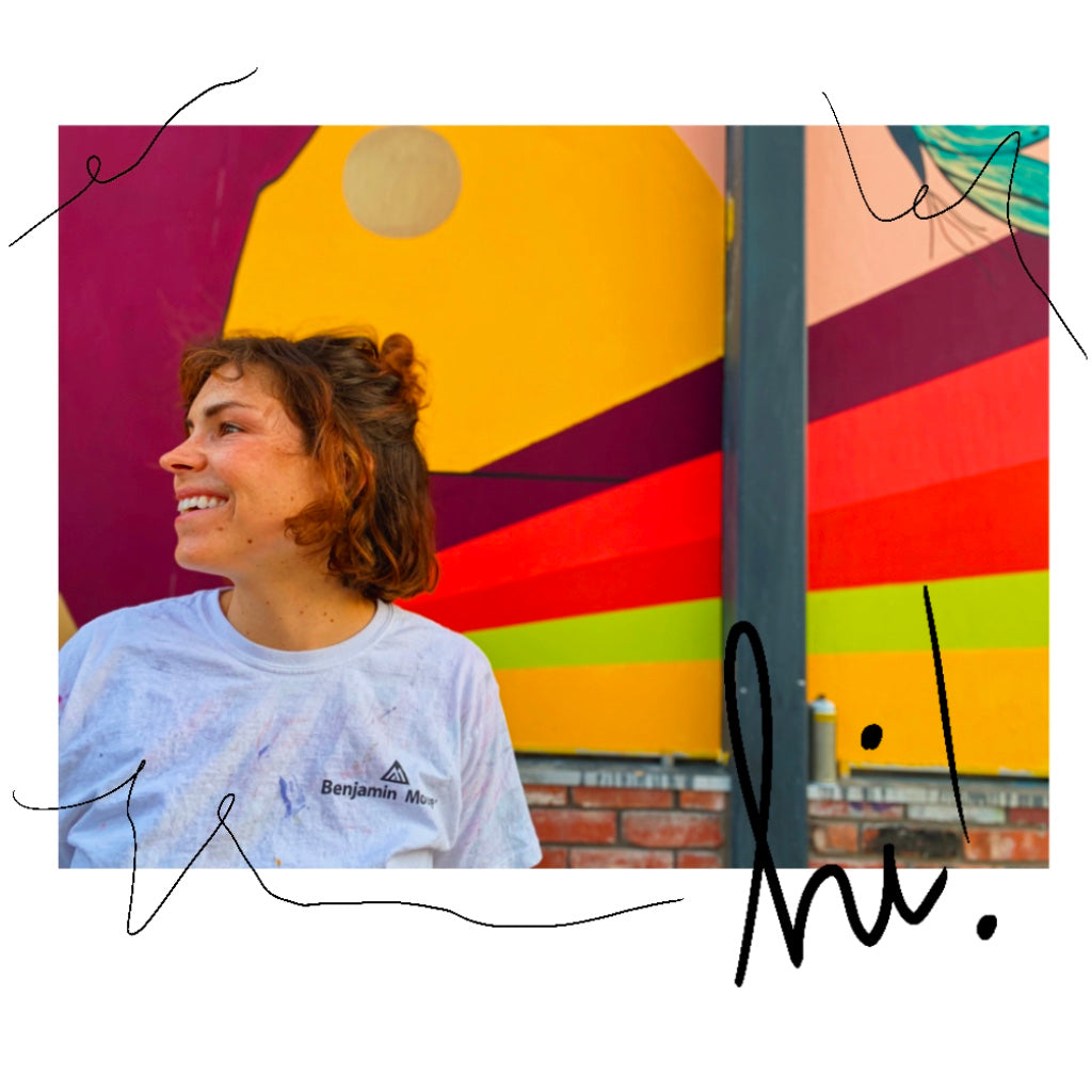 photo of a 30-year-old woman with a big smile, looking to the left. in front of a bright-colored mural that she painted. wearing a paint splattered tshirt.