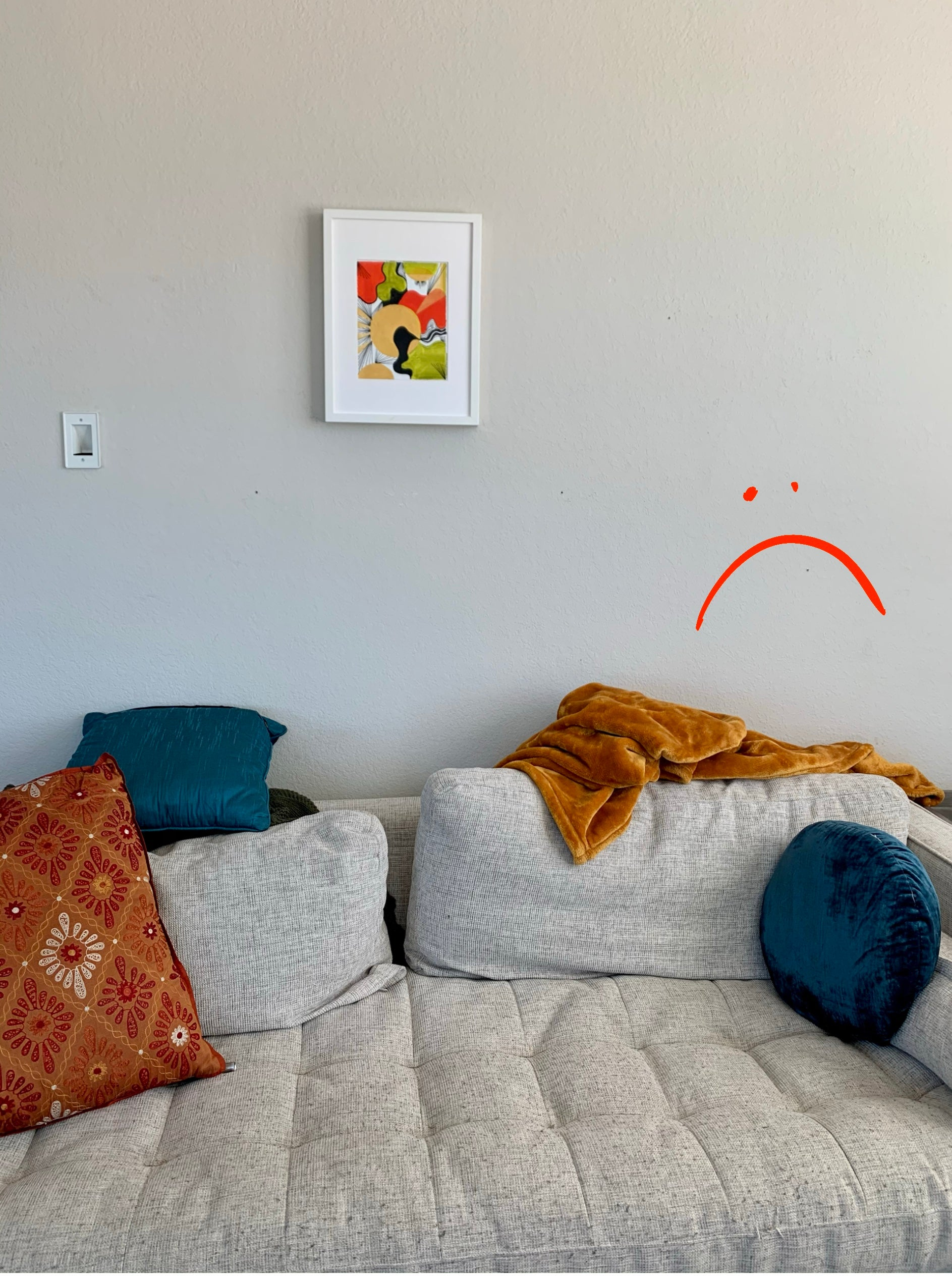 Image of a very small artwork above a light grey couch, covered with blankets and pillows. Sad face drawn on top of photo to show that the art is too small for this space!