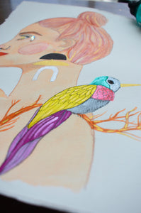Close up image of a mixed media portrait painting of a female Goddess embodying the Air Goddess. Painting features a face crystal, metallic details, spring colors like peach, turquoise and purple and lime green, and a playful bird and tree branch.