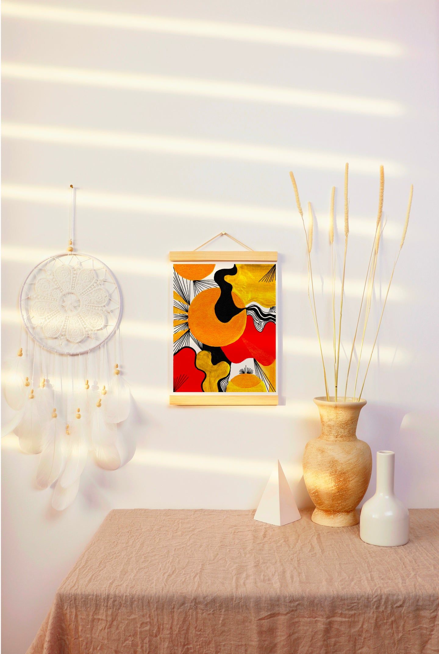 Bright, white room with simple neutral decor, including a tan vase, white dream catcher and tan table cloth. Room pops with vibrant painting, hanging in a poster hanger. Painting features abstract organic green, red, black and gold shapes. Detailed with black lines. This design any room pop with energy!