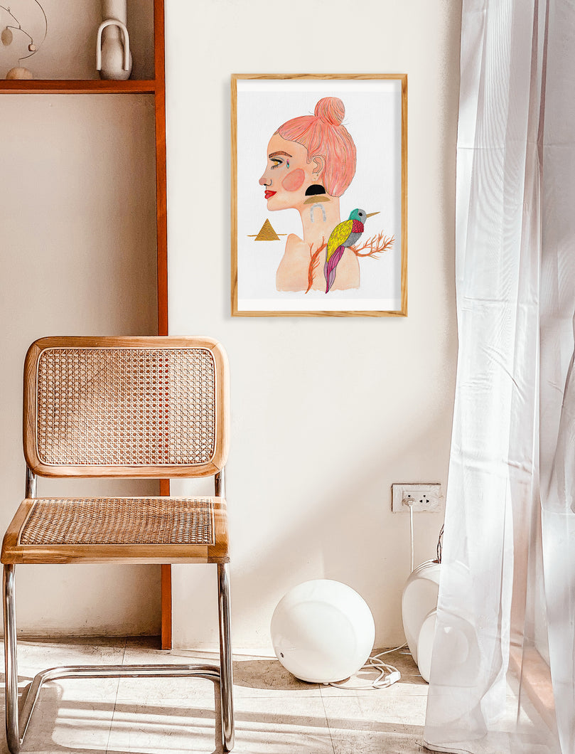 White and tan room with simple decor, including a wicker chair and white curtains. Room pops with a vibrant framed painting. Featuring female portrait painting, Mixed media portrait painting of a female Goddess embodying the Air Goddess. Painting features a face crystal, metallic details, spring colors like peach, turquoise and purple and lime green, and a playful bird and tree branch.
