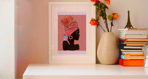 Image of a bookshelf featuring a stack of books, bright orange flowers, and a vibrant framed artwork that pops! Collaged mixed-media portrait of a black woman with a colorful bird on her shoulder. Light pink background and slightly textured. In honor of Black Lives Matter.