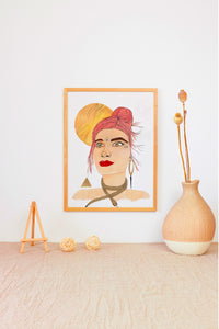 Simple minimalist design, featuring a tan cloth-covered table, and minimalist decor. Vibrant framed mixed media painting makes image pop. Mixed media original painting of a red-haired woman (Goddess) embodying the Fire Goddess. Features a real face crystal, firey colors like reds, oranges, yellows and golds. Also includes a gold shiny moon, gold snake necklace, and gold fire element symbol.