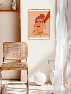 White and tan room with simple decor, including a wicker chair and white curtains. Room pops with a vibrant framed painting. The painting is a stylized portrait of a female face and shoulders, embodying the Fire Goddess. Features multiple real face crystals, firey colors like reds, oranges, yellows and golds. Also includes a gold shiny moon, gold snake necklace, and gold fire element symbol. The background is a soft mauve color and slightly textured.
