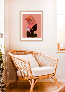 White and tan room with simple decor, including a wicker chair. Room pops with a vibrant framed artwork. Collaged mixed-media portrait of a black woman with a colorful bird on her shoulder. Light pink background and slightly textured. In honor of Black Lives Matter.