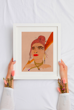Load image into Gallery viewer, Photo of a woman's hands holding a white frame with a vibrant painting. The painting is a stylized portrait of a female face and shoulders, embodying the Fire Goddess. Features multiple real face crystals, firey colors like reds, oranges, yellows and golds. Also includes a gold shiny moon, gold snake necklace, and gold fire element symbol. The background is a soft mauve color and slightly textured.