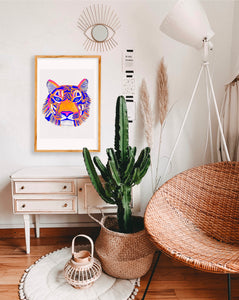 Bohemian living room, with a rich green cactus, wicker chair, tall white lamp, evil eye wall art and large wooden framed painting. The painting is vibrant and pops is the simple space.   Beautiful tiger artwork; features a colorful tiger head close up, blues, oranges and pinks, whimsical watercolor strokes. Slightly textured paper.