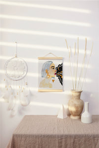 "Bright, white room with simple decor, featuring female portrait painting, hung on a poster hanger. Painting features a woman ""goddess"", gold triangle, and galaxy coming out of woman's mouth."