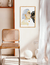 "Load image into Gallery viewer, White and tan room with simple decor, including a wicker chair and white curtains. Featuring female portrait painting, hung on a poster hanger. Painting features a woman ""goddess"", gold triangle, and galaxy coming out of woman's mouth."