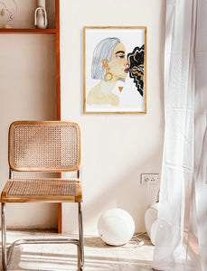 "White and tan room with simple decor, including a wicker chair and white curtains. Featuring female portrait painting, hung on a poster hanger. Painting features a woman ""goddess"", gold triangle, and galaxy coming out of woman's mouth."