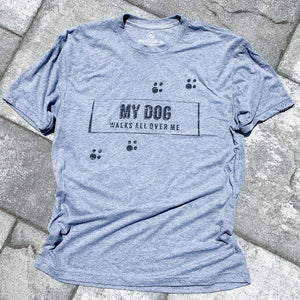 paw prints on front of tshirt. super soft vintage tshirt in grey . unisex grey triblend tshirt for men and women. dog lovers tshirt with my dog walks all over me quote. dog lovers tshirts. my dog walks all over me message. apparel for dog lovers.