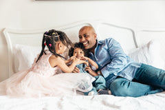 Reduce stress by sleeping better: Father playing with his kids on a bed