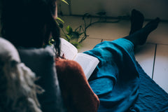 A woman sits comfortably on the floor reading a book ready for her hypnotherapy session