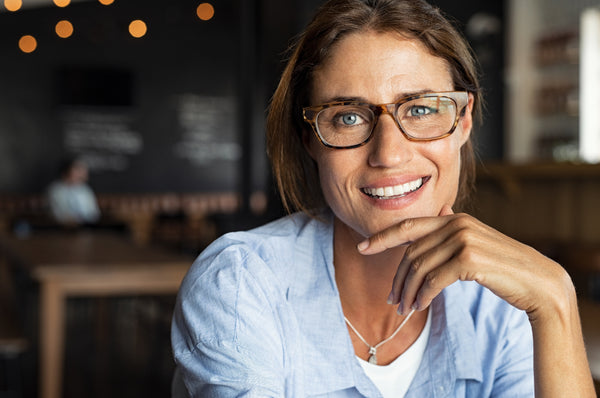 Portrait of happy mature woman wearing eyeglasses and looking at camera. Closeup face of smiling woman sitting in cafeteria with hand on chin.