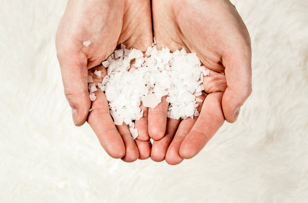 Close up view of man hands holding Magnesium Chloride vitamin salt flakes in palms hands, isolated on white soft fur background. Ingredient for making feet bath with Magnesium salt flakes. - Image