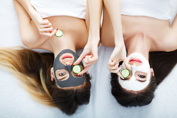 Home spa. Two women holding pieces of cucumber on their faces lying the bed.