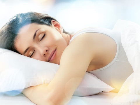 Woman sleeping arms wrapped around a pillow