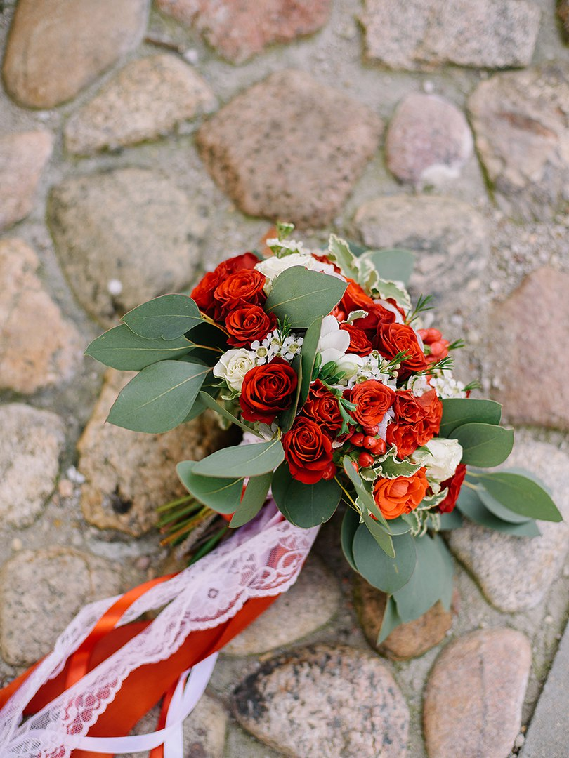 Bridal and prom bouquet with red mini roses, eucalyptus, freesia and lisianthus.