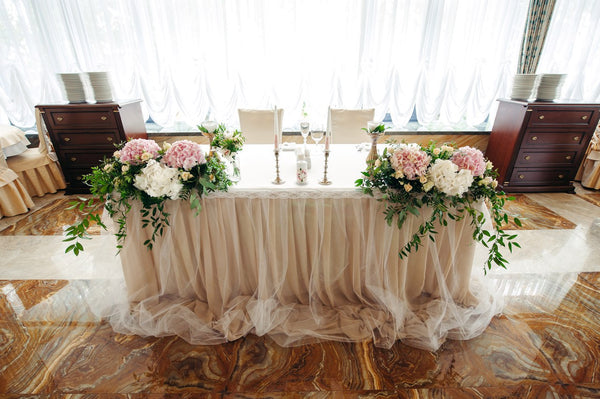 One of the most popular trends in wedding at the moment is having a sweetheart table.Some couples are choosing to have ornate, luxurious sweetheart tables with lush floral garlands that spill onto the floor, candles and sequined table linens, while others are choosing to have plush, vintage chairs seated around a rustic wooden table with a scatter of lanterns for a more simple, yet still elegant. Includes: Flower arrangements: white and pink hydrangea, white lisianthus, creamy mini roses,assorted greens. Ca