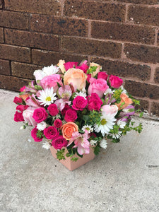 "A sweet treat any day of the week! Warm, rich colors of pink, peach and white are contrasted with fresh green - a welcome combination for any occasion. Send it to sweeten a best friend's birthday, say ""hi"" to mom, or delight your better half.  Includes:  Hot pink mini roses, peach roses, pink alstroemerias, white daisies, assorted greens. Floral box"