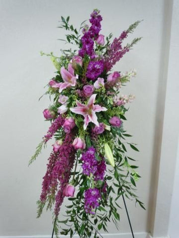 Funeral arrangement on the holder  with purple roses, lilies and delphinium.